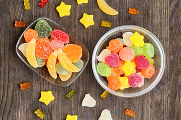 Fototapete - Bowls with delicious jelly candies on wooden background