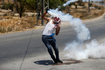 A Palestinian protester returns a tear gas canister fired by Israeli troops during clashes near the West Bank City of Ramallah