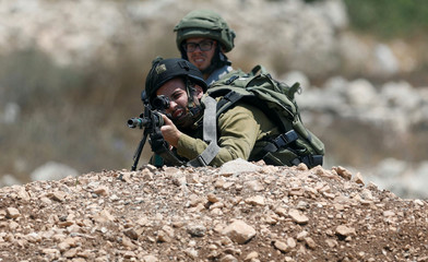An Israeli soldier aims his weapon during clashes with Israeli troops near the West Bank City of Ramallah