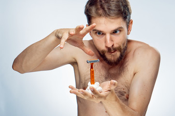 Young guy with a beard on a white isolated background holds a shaving foam and a razor