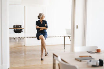 Businesswoman sitting on table in modern office