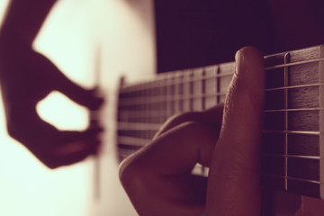 Man's hands playing on classical guitar against a background of white light (toned)