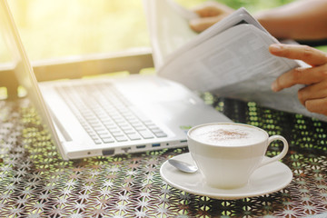 Stock photo :.Cappuccino coffee cup on a vintage table with laptop of a man reading a newspaper in the morning light.