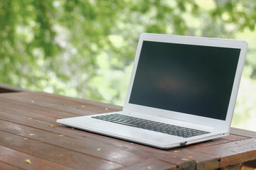 Stock photo :.Computer Laptop on wooden table with blur nature bokeh background, business technology concept