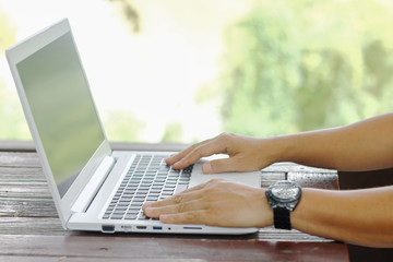 Stock photo :.Closeup image of a hands working and typing on laptop keyboard with blur nature background