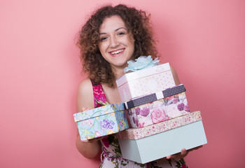 Beautiful elegant young woman in a pretty dress with presents posing over pink background. Woman holding gifts in her hands. Fashion spring summer photo.