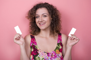 Beautiful elegant young woman in a pretty dress with business cards posing over pink background. Copy space. Fashion spring summer photo.