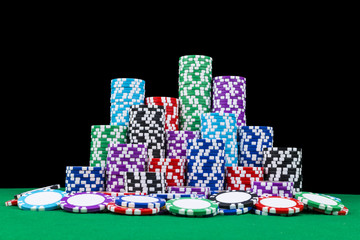 A set of poker chips stack on a green game table with a dice rolls. Black background. risk concept - playing poker in casino. Poker game theme