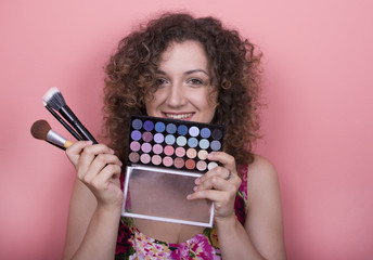 Beautiful elegant young woman in a pretty dress with makeup tools posing over pink background. Fashion spring summer photo.