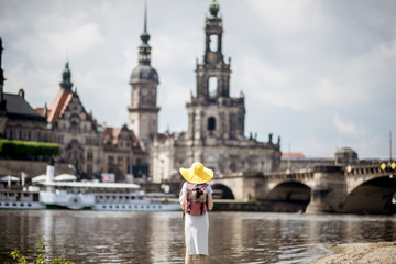 Young woman tourist in yellow hat standing back and enjoying great view on the old town of Dresden, Germany