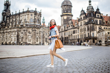 Young woman with photocamera walking on the Theaterplatz in Dresden, Germany