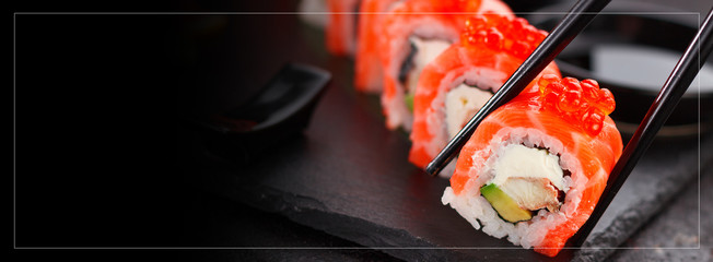 Japanese cuisine.Sushi roll with salmon eel and red caviar. One peace in chopsticks.