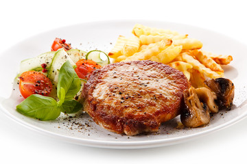 Grilled steak, French fries and vegetable salad on white background