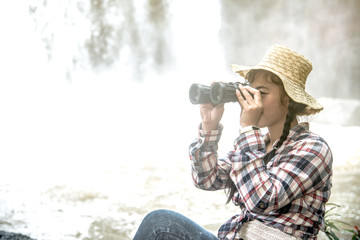 Young Asian traveler woman looking a binoculars in happiness and sitting on a rock of waterfall.