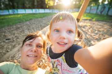 Funny little girl with her happy mother are taking selfie