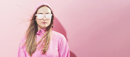Wall Mural - Girl in trendy painted glasses in pink jacket on a pink background