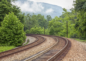 Curving Double Railroad Tracks through Foggy Mountains