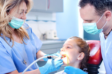 Dentists examining girl patient's teeth at dental office.