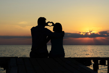 Young loving guy and girl sit on the bridge by the sea and skip a silhouette of the heart in the sky at sunset sun and sun rays. Family happy couple. Love and romance