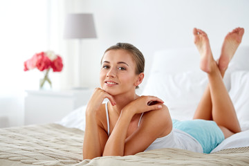 Fototapete - happy young woman lying on bed at home