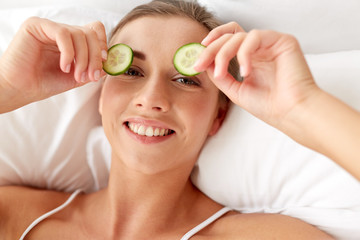 beautiful woman applying cucumbers to eyes at home