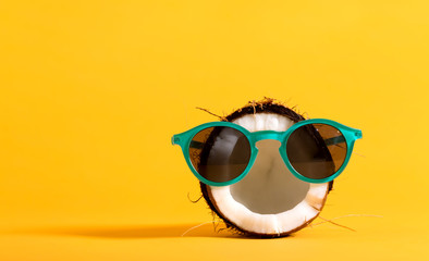 Fresh coconut wearing sunglasses on a bright yellow background