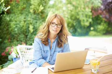 Home office. Shot of a happy middle aged woman using laptop while working in the garden.