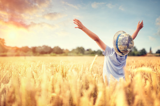 Boy with raised arms in wheat field in summer watching sunset
