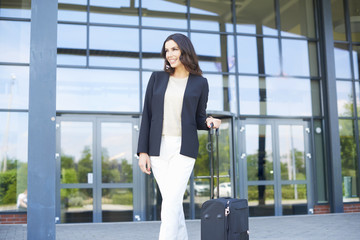 Shot of a young businesswoman standing in front of the office building and waiting for the taxi.c