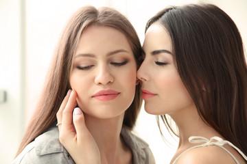 Lovely lesbian couple together on light background