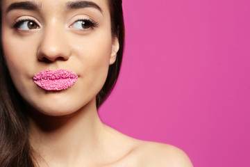Beautiful young woman with lips makeup on color background