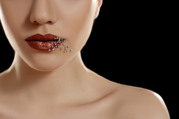 Lips of beautiful young woman covered with sprinkles on dark background, closeup