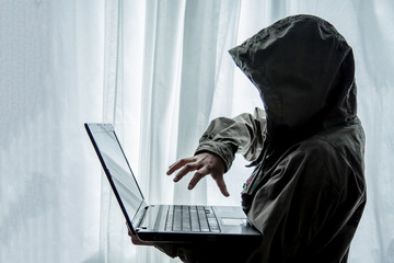 Hacker or terrorists  in hood with masked working on dark digital his on computer. Hacking the system cyber crime concept .
