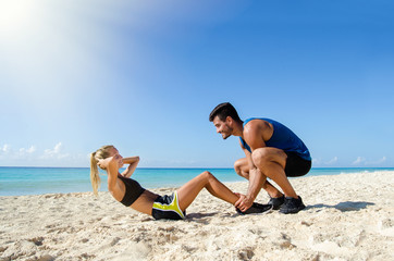 Young couple training at the beach
