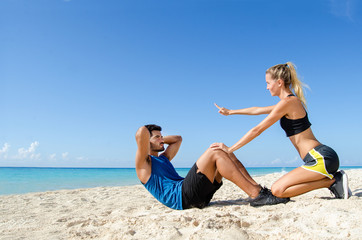 Couple making abdominal crunch at the beach