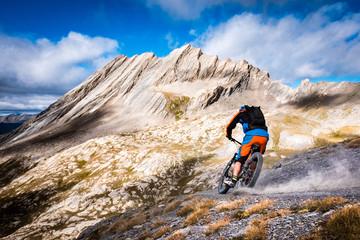 Epic Alpine Mountain Biker throws dust as he speeds towards a stunning mountain