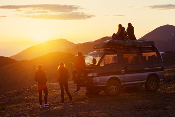 Travel concept with friends, sunset and car Wall mural