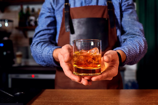 Hands of a bartender at bar restaurant with glass whiskey