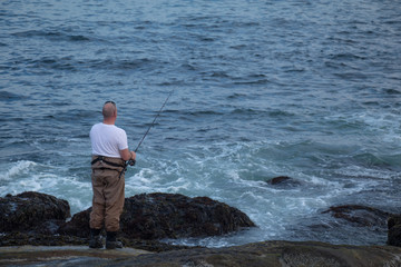 Alternative view of a man fishing in a high tide