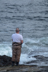 A man fishing in a high tide