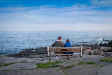 Two lovers peacefully sitting on a bench by the ocean