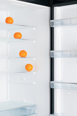 Open fridge with ripe tangerines