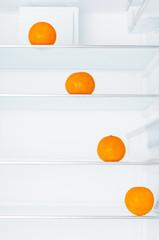 Ripe tangerines on shelves in fridge
