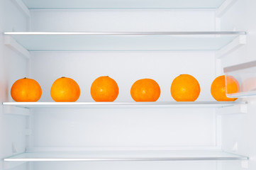 Empty fridge and ripe tangerines on shelves