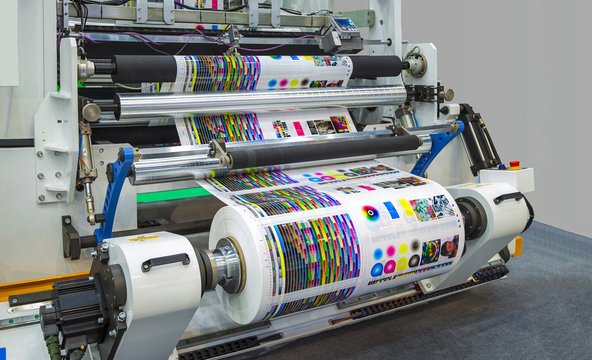 Large offset printing press or magazine running a long roll off paper in production line of industrial printer machine.