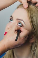 makeup artist applying eyeliner on girl face
