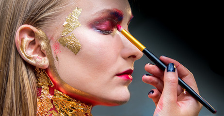 Artistic professional make up applies eye shadow. Beautiful woman face.