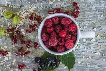 different berries in bowl and rustic background top view
