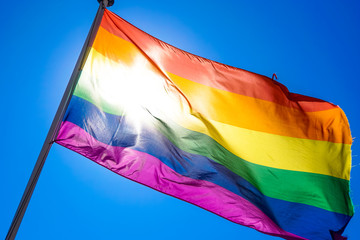 Rainbow flag waiving in the wind with sun shining through it