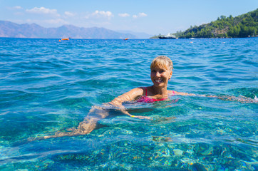 A lady enjoys in the sea. Lady splashing sea water and enjoying life during summer holidays on the tropical beach. Woman swim and relax in the sea.
